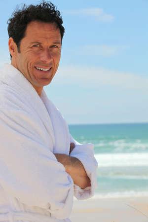 bath gown: Man n dressing gown stood on beach Stock Photo