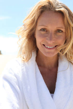 toweling: Smiling woman in toweling robe outdoors Stock Photo