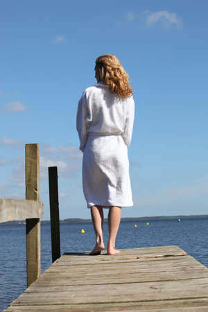 bath robes: Woman in a bathrobe standing on a wooden pier