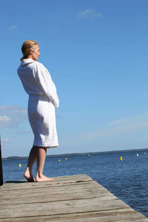 toweling: Woman in a toweling robe standing on a wooden jetty