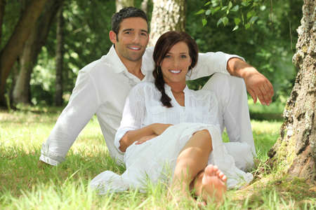 Couple in white sitting on the grass photo
