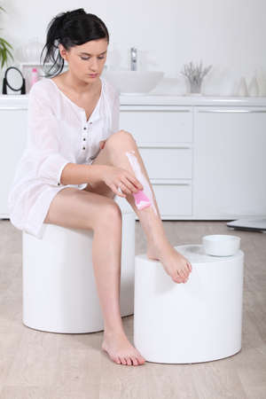 Woman using a hair removal cream on her legs photo
