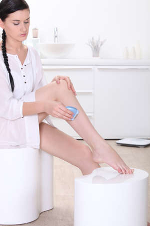 woman shaving her legs photo