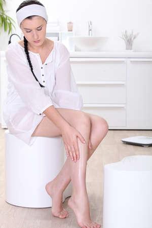 foot cream: portrait of a woman massaging her leg