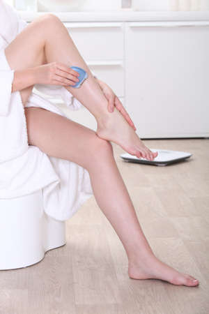 a woman shaving her legs photo