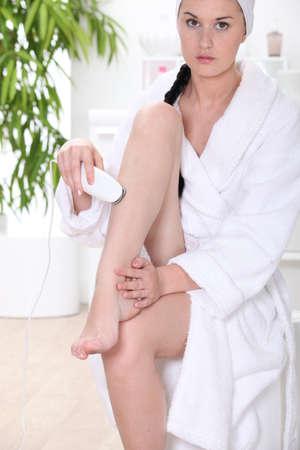 Woman using epilator in bathroom Stock Photo - 13864011