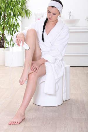 hairy legs: Woman removing leg hair in a bathroom