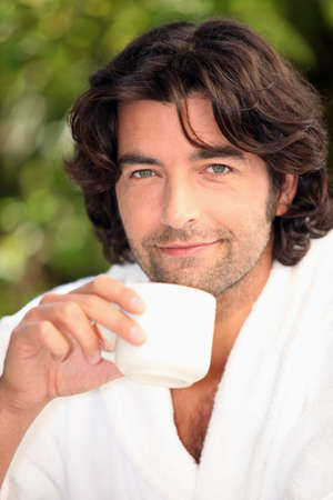 robes: handsome man drinking his coffee in the garden