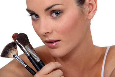 woman holding three make up brushes photo