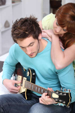 Woman beat guitar: Woman looking guy with guitar