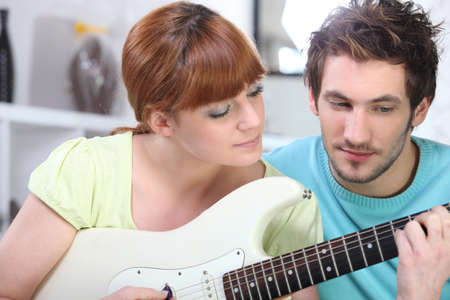 lesson: Man teaching a woman to play the guitar