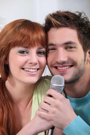 persona cantando: Pareja joven con un micr�fono