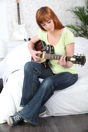 Young female guitarist at home photo