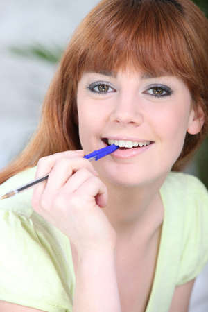 Portrait of a woman with a pen in her mouth photo