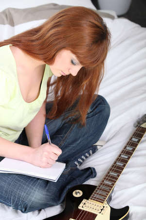 Girl with guitar composing a song photo