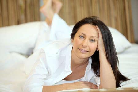 ennui: Brunette relaxing in bed