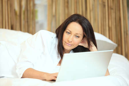 Woman with a laptop on her bed photo