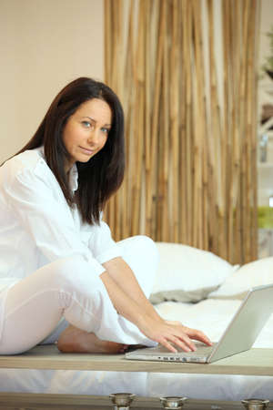implemented: Woman sitting in bed with computer