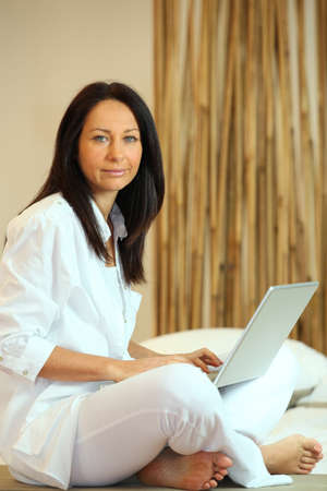 pies bonitos: Mujer sentada en el suelo con la computadora Foto de archivo