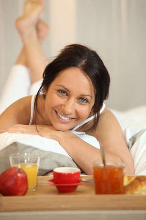 Brunette woman with breakfast in bed photo