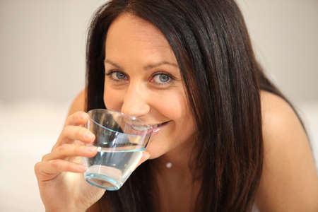 Brunette drinking a glass of water photo