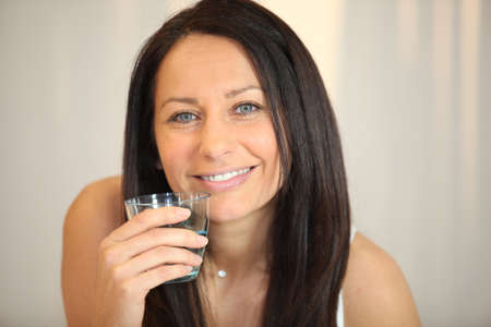 apprehend: Brunette woman with glass of water