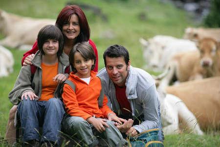 Familia joven sentado en un campo de ganado photo