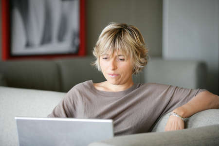 Woman using a laptop on the sofa Stock Photo - 13881408