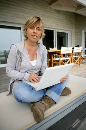 Blond woman sat on patio with latop photo
