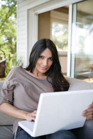 Woman using her laptop on outdoors sofa photo