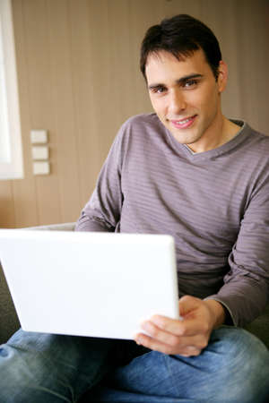 outworking: Man sat at home with a laptop