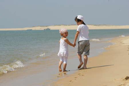 Cute boy and girl walking on the beach photo