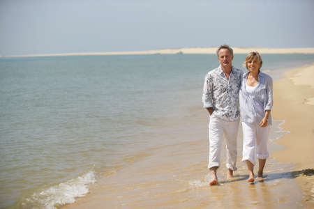 Middle-aged couple strolling along the shore photo