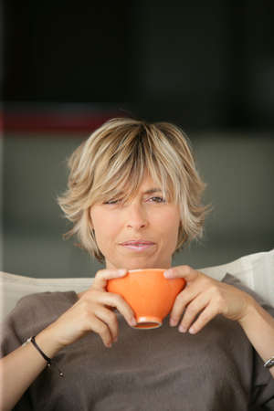 woman drinking tea on the sofa photo