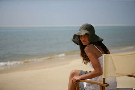 folding chair: Woman sitting on a chair on the beach Stock Photo