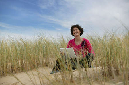 Woman using a laptop in a sand dune photo
