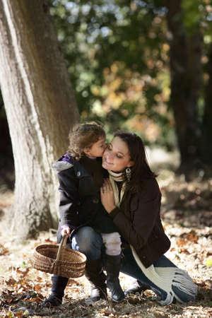 Little girl kissing her mum in woods photo