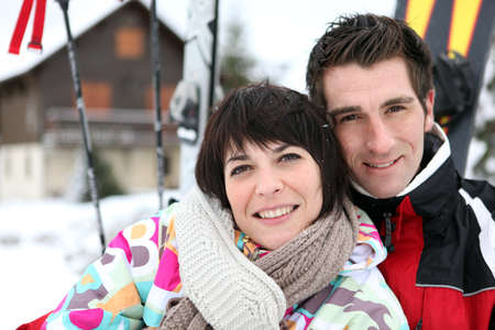 Couple in front of a ski cabin photo