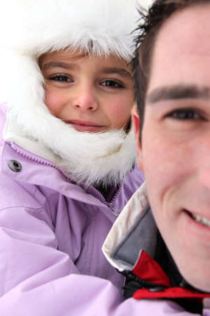 Portrait of a man with little girl by wintertime photo