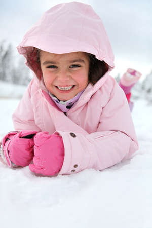Little girl playing in the snow photo