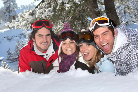 Four friends laying in the snow photo