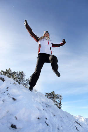 Woman jumping in the snow Stock Photo - 13881289