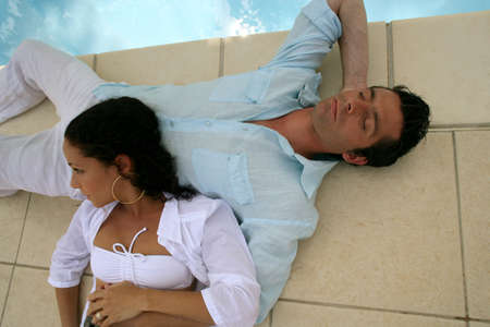 Couple relaxing by the pool photo