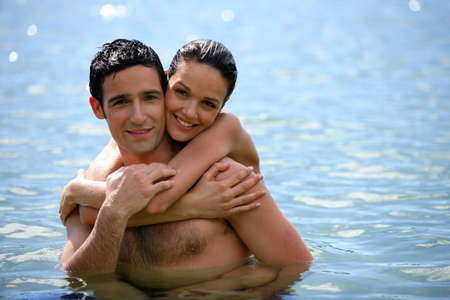 Young couple hugging in the water photo