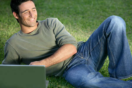 Happy man sat in field with laptop photo