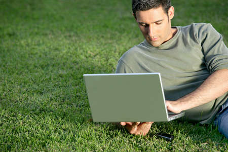 Man relaxing in field with laptop photo