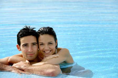 young boy in pool: beautiful couple in a swimming pool