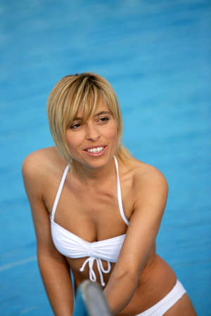 Blond woman getting in to swimming pool photo