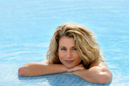 Beautiful blond woman leaning on the poolside photo