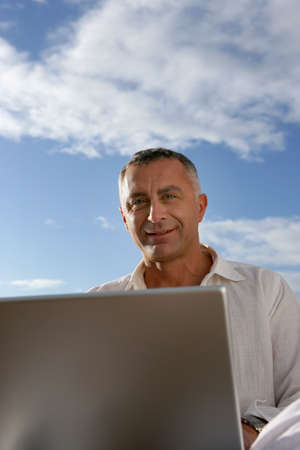 closely cropped: mature man working outdoors with laptop
